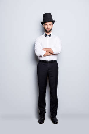 Full size fullbody portrait of stylish attractive magician in tophat having his arms crossed, looking at camera, isolated on grey background