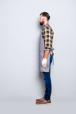 Full size body snap, half face side view portrait of attractive calm carpenter with hairstyle in safety glasses, jeans, isolated grey background Stock Photo