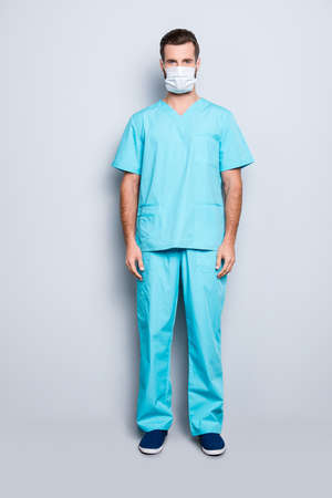 Full size fullbody portrait of attractive handsome man in sterile mask and blue lab suit, looking at camera, isolated on grey background