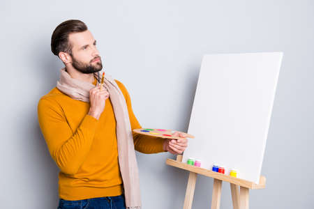 Portrait of minded ponder artist having brushes and palette in arms holding hand near chin, imagine future picture, isolated on grey background 写真素材 - 104188027