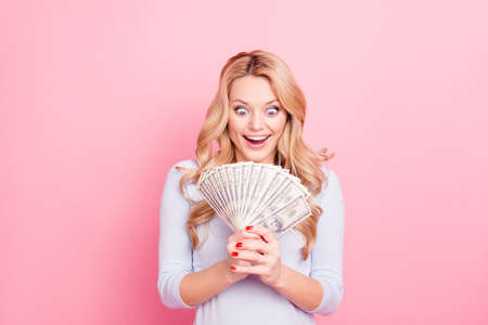 Portrait of astonished surprised crazy girl with wide open eyes, mouth looking at much money in her hands, isolated on pink background. Jack-pot, casino player concept