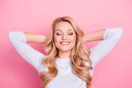 Retrato de niña alegre positiva con peinado moderno maquillaje natural radiante sonrisa cogidos de la mano detrás de la cabeza manteniendo los ojos cerrados soñando con viaje, viaje, viajar Foto de archivo