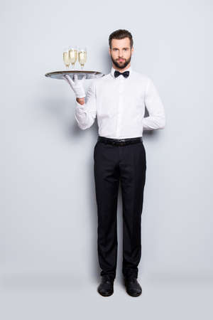 Full size fullbody portrait of concentrated man in classic white shirt and black bowtie holding hand behind the back and tray with three glasses of sparkling wine, isolated on grey background Banco de Imagens - 104188081