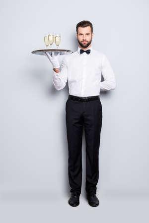 Retrato de cuerpo entero de tamaño completo de hombre concentrado en camisa blanca clásica y pajarita negra sosteniendo la mano detrás de la espalda y bandeja con tres copas de vino espumoso, aislado sobre fondo gris