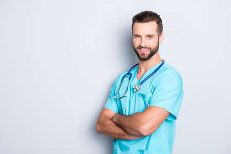 Portrait with copy space, empty place of positive cheerful man with stethoscope on his neck in blue lab uniform, having his arms crossed, isolated on grey background