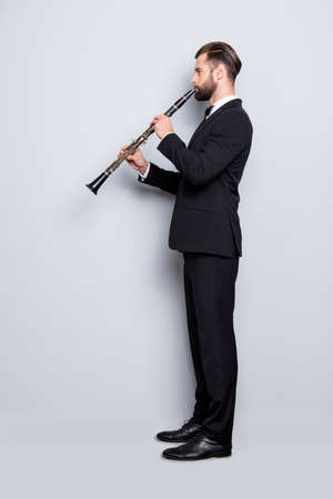 Side view half face, full size fullbody portrait of stylish talented musician with hairstyle in black tux with bow, pants, playing on bassoon, isolated on grey background