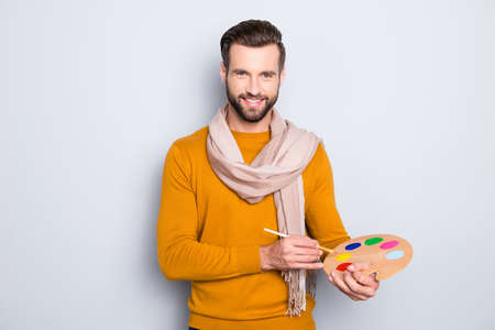 Portrait of positive attractive artist with stubble, hairstyle in sweater and scarf on neck using having colorful palette and brushed in arms, isolated on grey background
