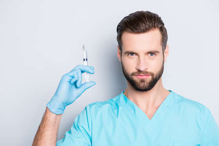 Portrait of attractive handsome medic with stubble in lab blue uniform showing having syringe in hands, looking at camera, isolated on grey background
