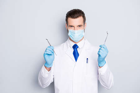 Portrait of successful handsome dentist in white lab coat with blue tie having, showing, holding tools for teeth treatment with hands, looking at camera, isolated on grey background Stock Photo