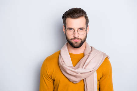 Portrait of stylish attractive stylist in sweater and gasses with scarf around neck looking at camera isolated on grey background Stock Photo