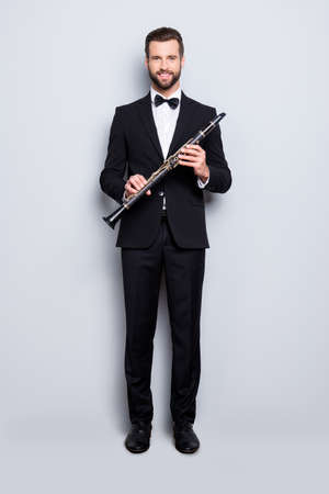 Full size, fullbody portrait of stylish, talented, cheerful musician with hairstyle in black tux with bowtie, pants, shoes holding bassoon in hands, looking ta camera, isolated on grey background