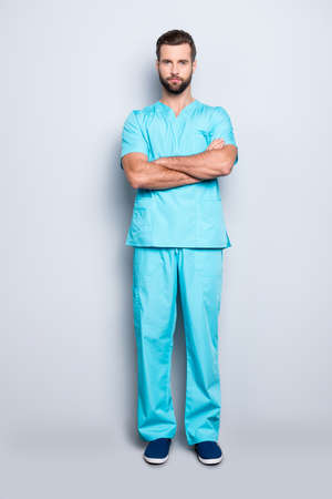 Full size body portrait of attractive concentrated man in blue lab suit, having his arms crossed, looking at camera, isolated on grey background