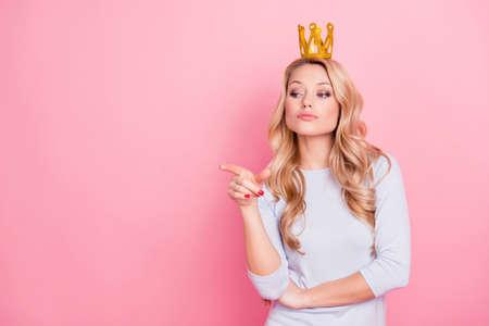 Retrato con copyspace lugar vacío de confianza orgullosa mujer arrogante con corona de oro en la cabeza apuntando con el dedo índice, señorita quiero, aislado sobre fondo rosa