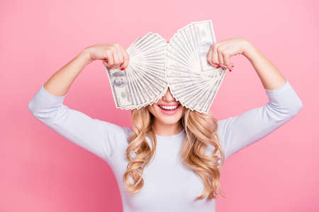 Portrait of crazy playful foolish girl with beaming smile holding fans from much money in hands cover her eyes isolated on pink background
