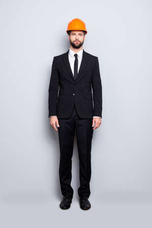 Full length size fullbody portrait of attractive strict stylish investor with stubble in hard hat, black tux, tuxedo with tie, isolated on grey background Imagens