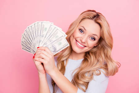 Portrait of charming pretty girl in casual outfit holding fan of a lot of money for shopping in hands looking at camera, isolated on pink background 版權商用圖片