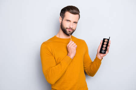 Portrait of ponder minded dreamy visagist in pullover with hairstyle having palette of shadow in hand, looking at camera isolated on grey background