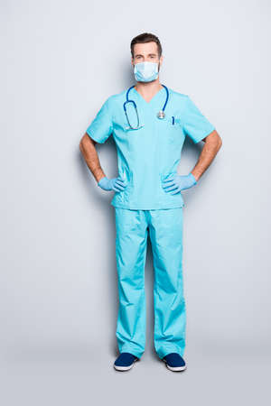 Full size body portrait of attractive handsome man in sterile mask and blue lab uniform, holding arms on waist, looking at camera isolated on grey background