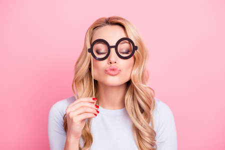 Portrait of cute lovely flirting girl having black carton glasses on stick blowing sending kiss with pout lips and close eyes isolated on pink background 写真素材