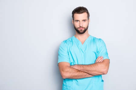 Portrait with copy space, empty place of virile harsh man with stubble in blue lab uniform, having his arms crossed, looking at camera isolated on grey background