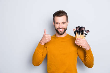 Portrait of attractive joyful visagist with bristle showing thumb up with finger having verity of brushes in arm, approve, advice, standing over grey background