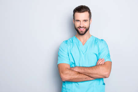 Portrait with copyspace, empty place of  joyful cheerful man with stubble in blue lab uniform, having his arms crossed, looking at camera isolated on grey background Stock Photo