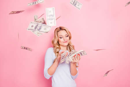 Portrait of carefree girlfriend, student wasting stack of much money, winner in casino lottery, having a lot of hundred dollars isolated on pink background Stockfoto