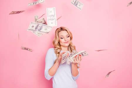 Portret van zorgeloze vriendin, student verspillen stapel veel geld, winnaar in casinoloterij, met veel honderd dollar geïsoleerd op roze achtergrond