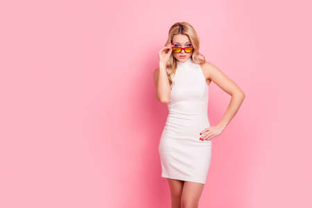 Portrait with copy space of cool business chick in elegant fitting white dress holding eyelet looking out glasses on her face at camera isolated on pink background