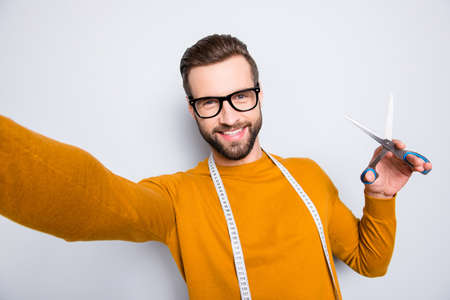 Self portrait of cheerful joyful attractive dressmaker shooting selfie on front camera holding scissors in hand and centimeter on neck, having fun leisure video-call, isolated on grey background