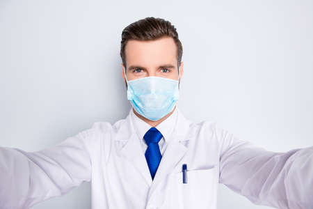 Self portrait of creative funny dentist in white lab coat, blue, tie, protective face mask shooting selfie on smart phone, having rest relax video call, isolated on grey background