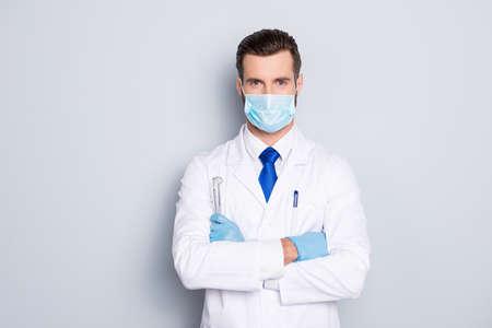 Porträt des attraktiven gutaussehenden Zahnarztes mit Frisur in der schützenden Gesichtsmaske, im weißen Laborkittel, in der blauen Krawatte, die Ausrüstungen in verschränkten Armen hält, lokalisiert auf grauem Hintergrund