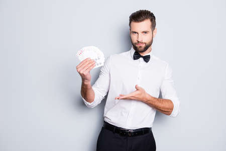 Portrait of stylish trendy croupier with hairstyle in formal wear having, showing with palm set of cards in hands, isolated on grey background, looking at camera