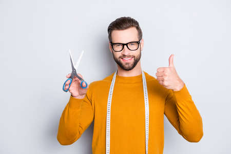 Portrait of positive cheerful dressmaker having centimeter on neck and scissors in hand showing thumb up with finger isolated on grey background. Recommend approve concept