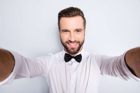 Self portrait of stylish trendy magician shooting selfie on smart phone with two arms, wearing white t-shirt and black bowtie, isolated on grey background