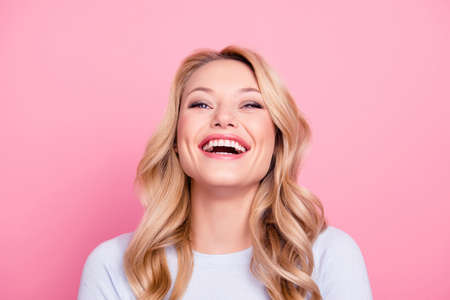 Portrait of foolish positive girl with modern hairstyle laughing sincerely with beaming smile isolated on pink background. Mood inspiration enjoyment pleasure concept
