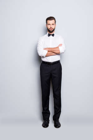Full size body portrait of stylish modern croupier in white shirt, bowtie, black pants, having his arms crossed, looking at camera, isolated on grey background