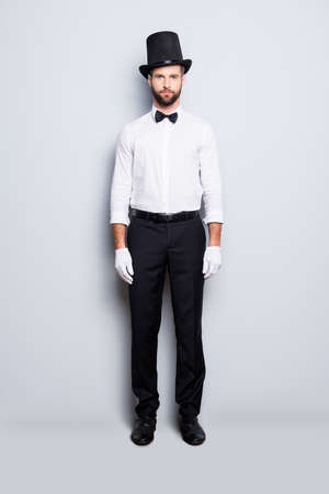 Full size fullbody portrait of stylish attractive magician in tophat, formal wear, bow, looking at camera, isolated on grey background Stock fotó