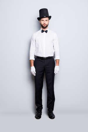 Portrait de plein corps de l'élégant magicien attrayant en tophat, tenue de soirée, arc, regardant la caméra, isolé sur fond gris Banque d'images - 104188627