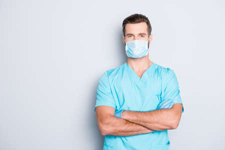 Portrait with copyspace, empty place of attractive handsome man in sterile mask and blue lab uniform, having his arms crossed, looking at camera isolated on grey background