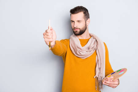 Portrait of creative concentrated artist with bristle in sweater and scarf on neck using, having colorful palette, brushed in arms, analyzing, expertising pic, isolated on grey background Stock Photo