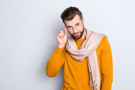 Portrait of modern confident stylist with scarf around neck looking out glasses at camera isolated on grey background holding hand on eyelet of spectacles on his face Stock Photo