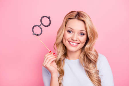 Portrait of sweetpretty student, cheerful, foolish positive girlfriend having black carton glasses on stick in hand looking at camera isolated on pink background