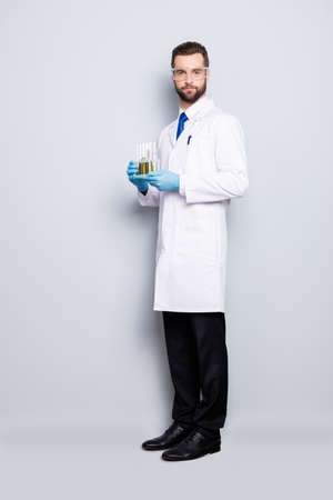 Full size fullbody portrait of attractive stylish scientist in white lab coat, black pants, shoes, tie holding test tubes with multi-colored liquid, looking at camera, isolated on grey background Imagens