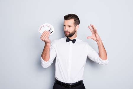 Portrait of cunning foxy magician with modern hairstyle and stubble in white shirt with bowtie holding set of cards in hand, making trick, focus, isolated on grey background Stock Photo
