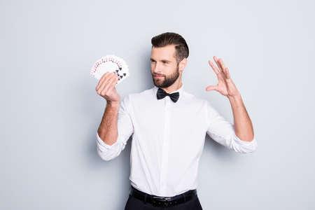 Retrato de astuto mago astuto con peinado moderno y rastrojo en camisa blanca con pajarita sosteniendo un juego de cartas en la mano, haciendo truco, enfoque, aislado sobre fondo gris