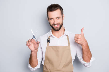 Portrait of cheerful positive barber with stubble in shirt having scissors in hand showing thumb up approve sign with finger, looking at camera, isolated on grey background 免版税图像