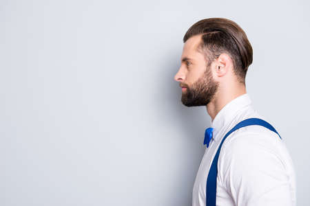 Profile side view portrait with copyspace, empty place for advertisement of famous concentrated singer wearing bow, shirt, suspenders, isolated on grey background