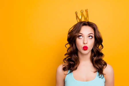 Portrait with copyspace empty place of funny stupid girl looking at crown on head with eyes sending kiss with pout lips isolated on yellow background advertisement concept Stockfoto