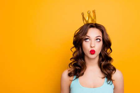 Retrato con copyspace lugar vacío de divertida chica estúpida mirando la corona en la cabeza con los ojos enviando un beso con labios fruncidos aislados en el concepto de anuncio de fondo amarillo Foto de archivo